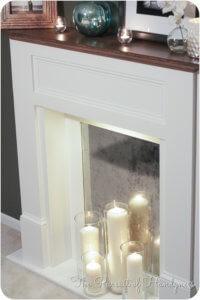 atrapa kominka z lustrzanym tłem i świecami różnej wielkości w szklanych świecznikach