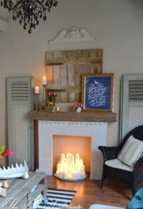 sztuczny kominek w rustykalnym wystroju i masą świeczek
