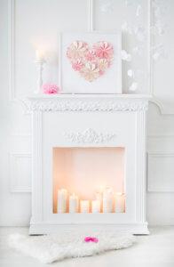 dziewczęcy kominek sztuczny dla dziewczyny ze świecami i różowym tłem